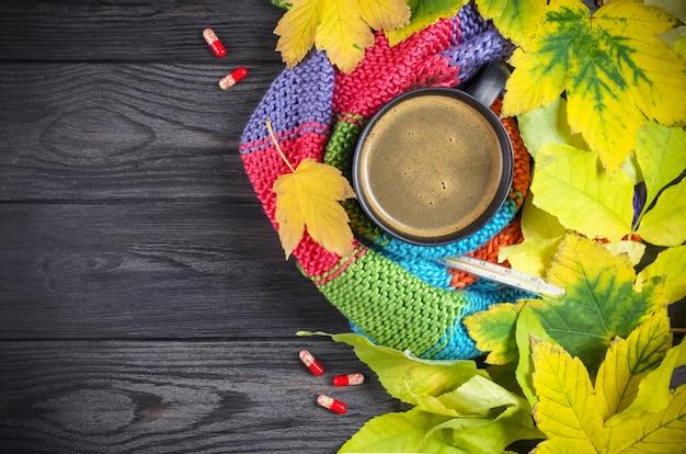 Natureza morta de outono: uma xícara de café quente e um termômetro embrulhado em um lenço quente, folhas amarelas. vista do topo