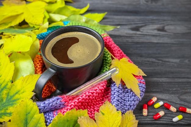 Natureza morta de outono: uma xícara de café quente e um termômetro embrulhado em um lenço quente, folhas amarelas.