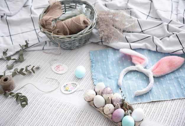 Natureza morta de páscoa com orelhas decorativas de coelhinho da páscoa, uma bandeja de ovos festivos e elementos decorativos