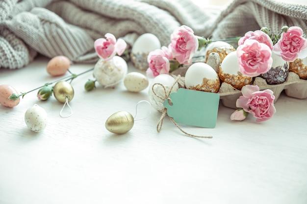 Natureza morta de páscoa com ovos de páscoa, flores frescas e elementos decorativos close-up