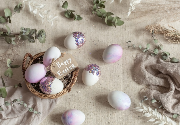 Natureza morta de páscoa com ovos decorados com lantejoulas em uma cesta de vime. feliz páscoa conceito