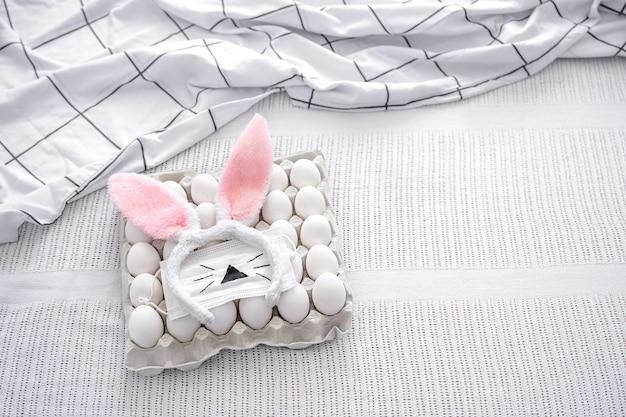 Natureza morta de páscoa com uma bandeja de ovos, orelhas decorativas de coelhinho da páscoa e uma máscara pintada