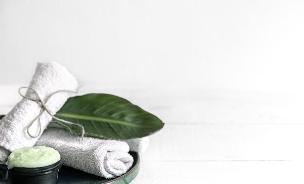 Natureza morta de spa com cuidados orgânicos da pele, folhas naturais e toalhas.