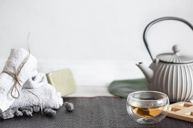 Natureza morta de spa com produtos para a pele do rosto e do corpo e fundo de chá