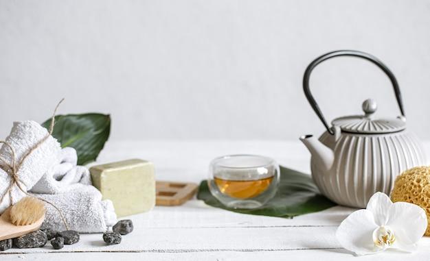 Natureza morta de spa com produtos para o rosto e corpo e chá.