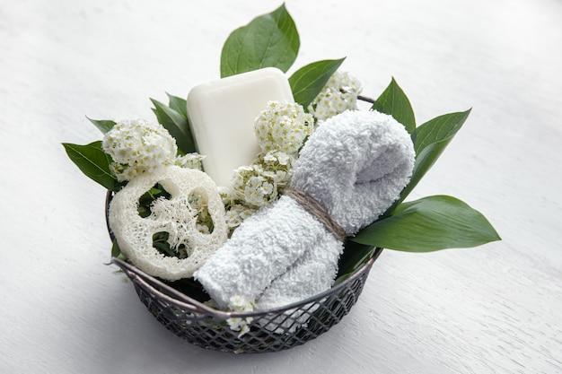 Natureza morta de spa com sabonete, bucha e uma toalha em uma cesta.