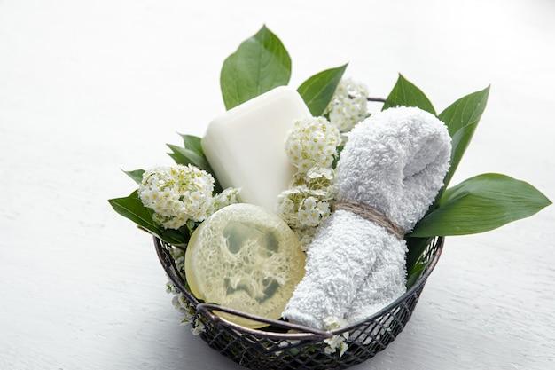 Natureza morta de spa com sabonete, bucha e uma toalha em uma cesta