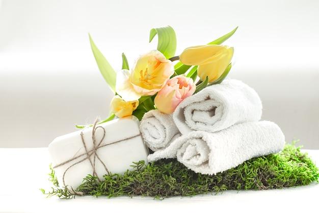 Natureza morta de spa com sabonete natural, toalhas e tulipas amarelas