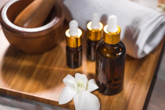 Natureza morta de spa com toalha, orquídea branca, óleo de banho