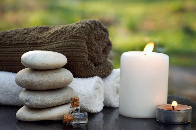 Natureza morta de spa com toalhas, vela acesa, óleo de banho e pedras de massagem no cenário de um jardim verde no verão