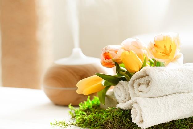 Natureza morta de spa de primavera com o aroma de um difusor de óleo moderno com toalhas.