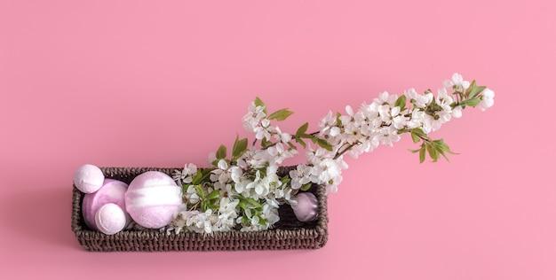 Natureza morta de spa em parede rosa com flores da primavera