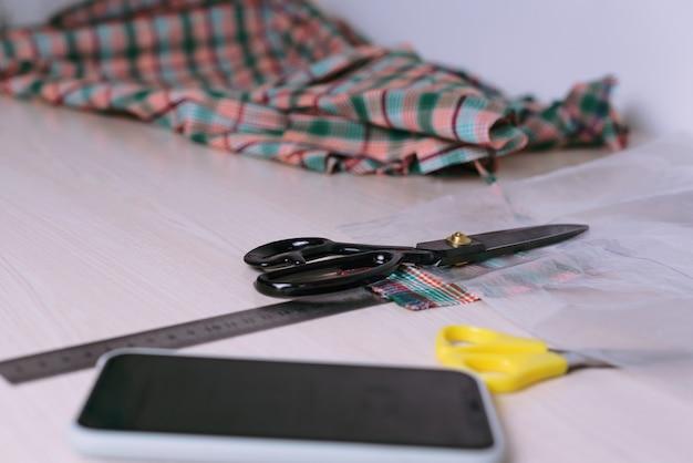 Natureza morta de tecido xadrez recortado e tesoura na mesa de madeira: local de trabalho do alfaiate