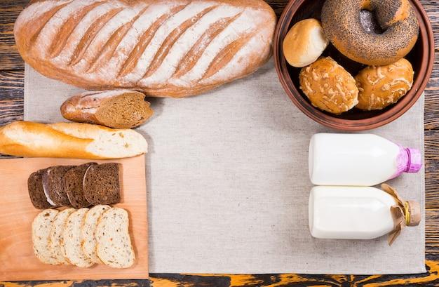 Natureza morta de uma grande variedade de pães frescos com garrafas de leite fresco e um copo cheio, visto de cima em um arranjo organizado