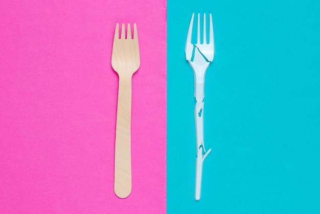 Natureza morta ecologicamente limpa minimalista. garfo de plástico quebrado e garfo de madeira no fundo rosa azul. talheres feitos de materiais naturais
