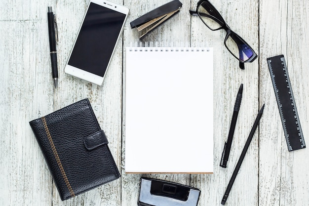 Natureza morta em preto e branco: abriu o bloco de notas em branco, cadernos, caneta, lápis, óculos, bolsa.