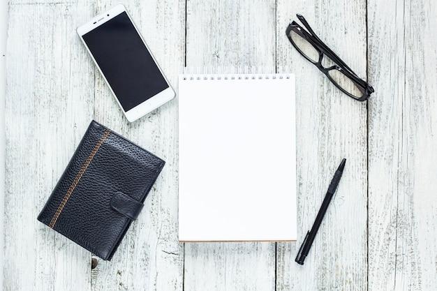 Natureza morta em preto e branco: bloco de notas em branco aberto, cadernos, caneta, lápis e óculos. vista superior, plana com espaço de cópia.