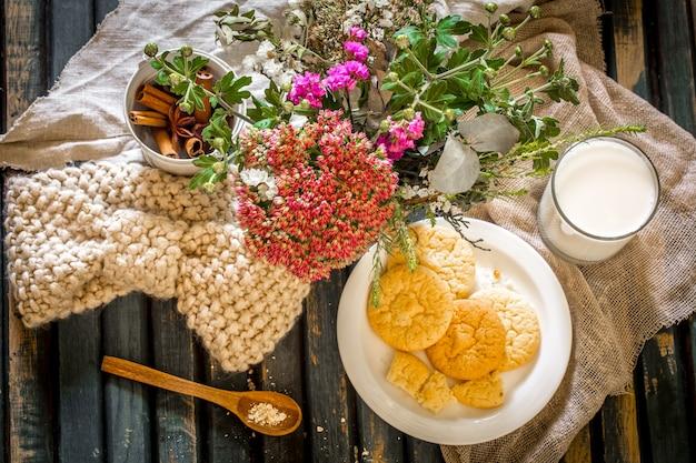 Natureza morta em uma mesa de madeira com prato de biscoitos e copo de leite