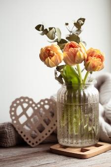 Natureza morta festiva com um arranjo de flores em um vaso e itens decorativos