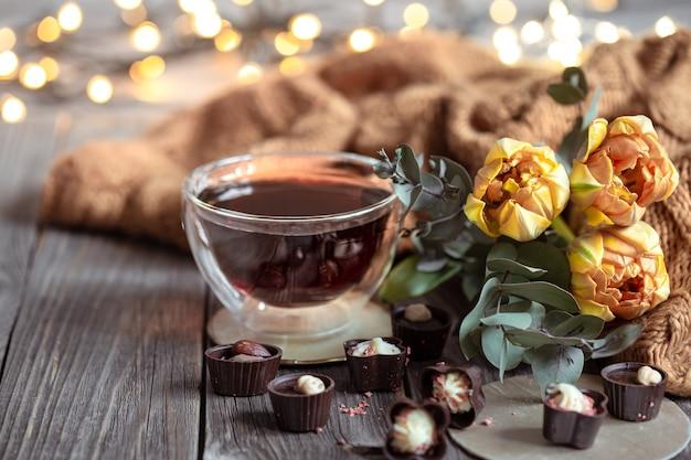 Natureza morta festiva com uma bebida em uma xícara, chocolates e flores