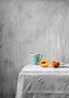 Natureza morta minimalista com pêssegos e caneca azul na mesa da cozinha contra a parede do grunge