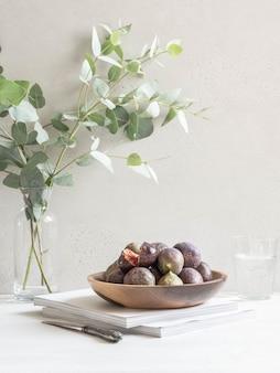 Natureza morta minimalista com uma placa de madeira cheia de figos maduros e um copo de água contra uma parede de luz. copie o espaço