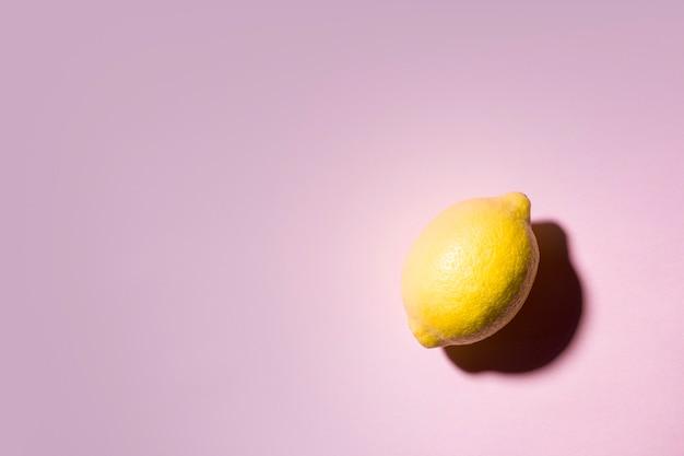 Natureza morta minimalista de um limão em fundo rosa