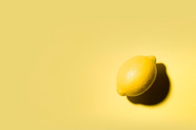 Natureza morta minimalista de um limão sobre fundo amarelo