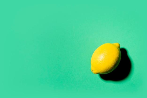 Natureza morta minimalista de um limão sobre fundo verde
