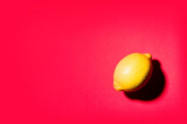 Natureza morta minimalista de um limão sobre fundo vermelho