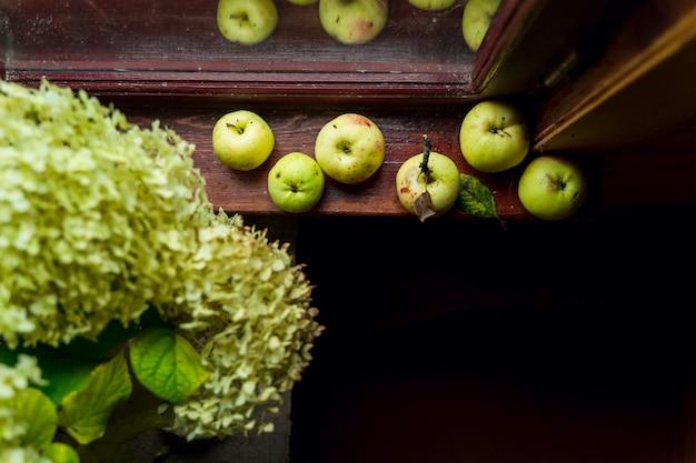 Natureza morta moderna com flores de hortênsia verde e maçãs verdes em um peitoril da janela de uma casa de campo de madeira