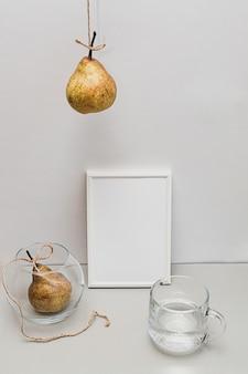 Natureza morta moderna com peras brancas e vazias em forma de moldura e um copo de água