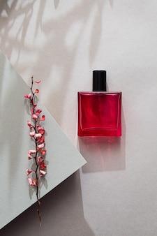 Natureza morta moderna com perfume e ramo rosa seco de bérberis