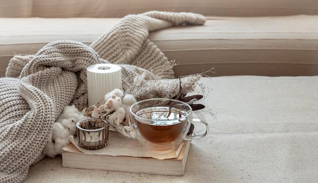 Natureza morta no estilo escandinavo com uma xícara de chá, um elemento de tricô e um livro