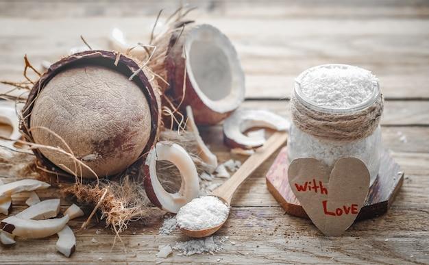 Natureza morta para dia dos namorados com coco e coração, colheres de madeira com coco no fundo de madeira
