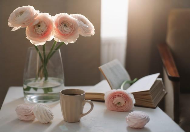 Natureza-morta romântica de primavera com flores, xícara de café, um livro e marshmallows