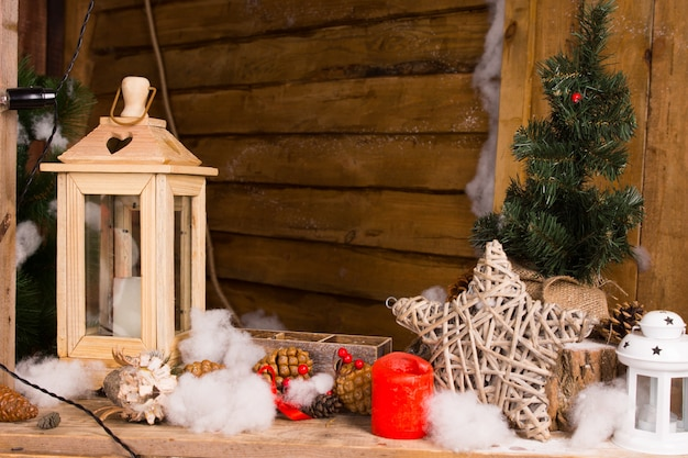 Natureza morta rústica de natal com decorações artesanais, incluindo uma lanterna de madeira, estrela de galhos entrelaçados, velas e neve sumaúma no interior de uma cabana ou cabana de madeira
