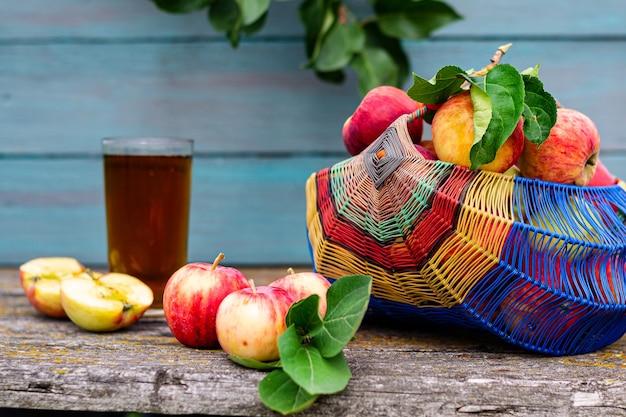 Natureza-morta rústica de verão, uma cesta de maçãs maduras de jardim em um fundo de madeira, suco de maçã em um vidro transparente. conceito de colheita sazonal.