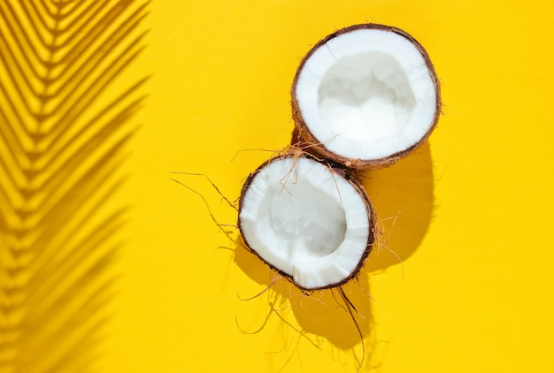 Natureza-morta tropical minimalista. duas metades de coco picado com sombras de folhas de palmeira em fundo amarelo. conceito de moda criativa.