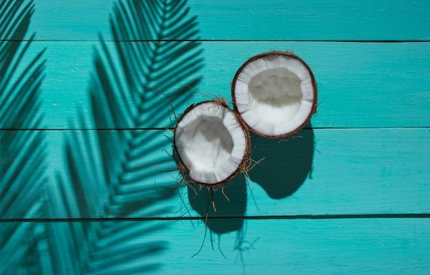 Natureza-morta tropical minimalista. duas metades de coco picado com sombras de folhas de palmeira sobre fundo azul de madeira. conceito de moda criativa.