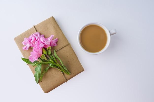 Natureza-morta vintage romântica com linda caixa de presente embrulhada com papel artesanal marrom e decorada com flor rosa sobre fundo branco