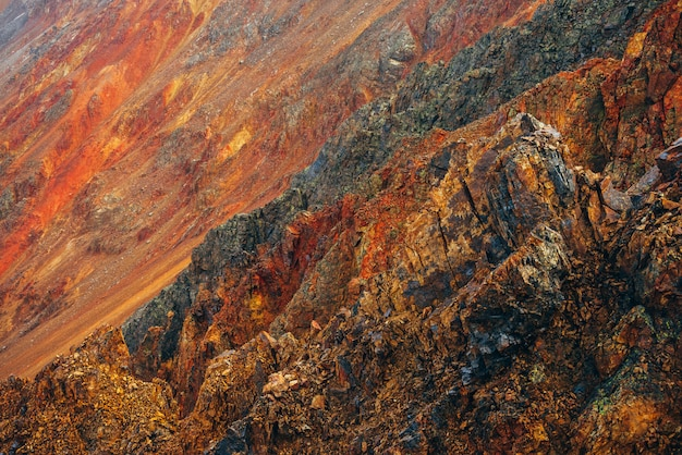 Natureza multicolor vívida da grande montanha rochosa com rochas pontudas. superfície do quadro completo de close-up de parede áspera montanha gigante. pedras vermelhas laranja amarelas. belo cenário natural das montanhas rochosas.