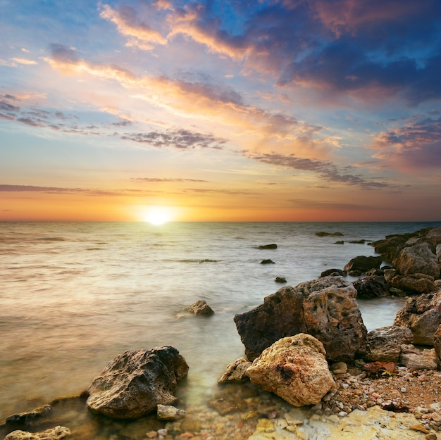 Natureza paisagem de mar e rocha ao pôr do sol.