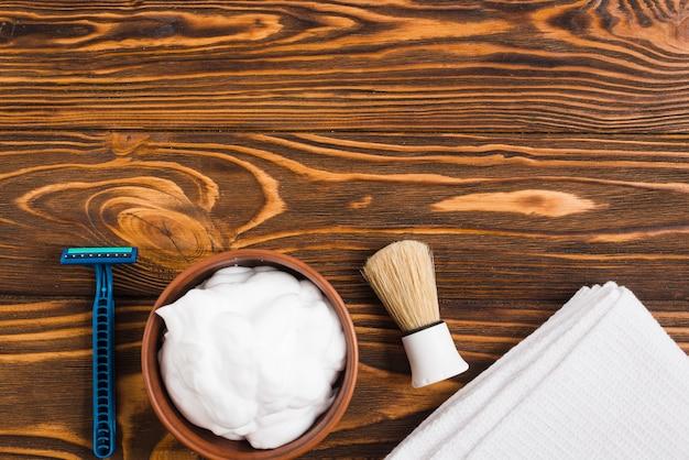 Navalha azul; espuma; pincel de barbear e branco guardanapo dobrado contra a superfície de madeira