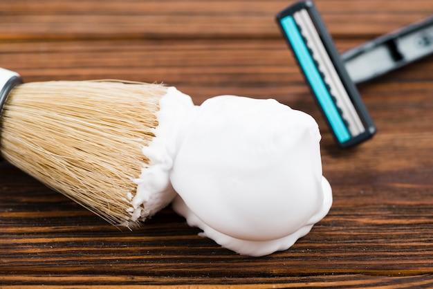 Navalha e pincel de barba com espuma no fundo de madeira
