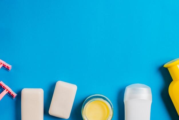 Navalha; sabonete; frascos de hidratante e shampoo em fundo azul