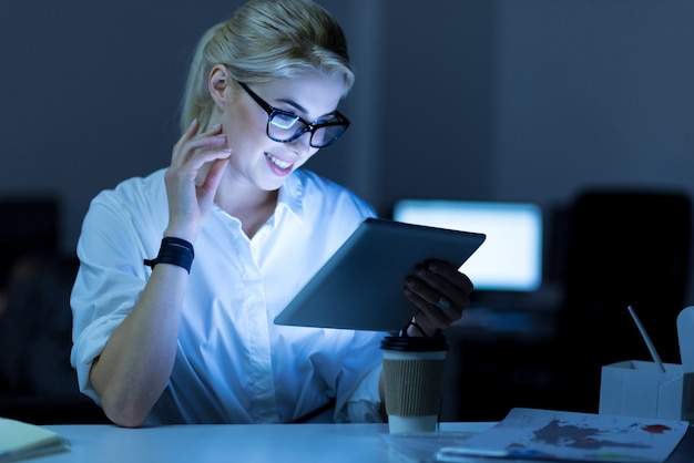 Navegar em busca de novas ideias. positiva, encantadora e sorridente, mulher de ti sentada no escritório usando um tablet enquanto trabalhava no projeto