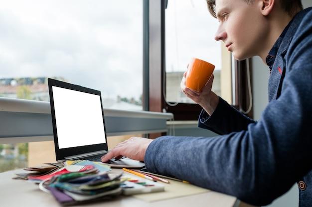 Navegar na internet. navegar na web para obter informações. designer relaxado bebendo café em seu local de trabalho. laptop com tela branca