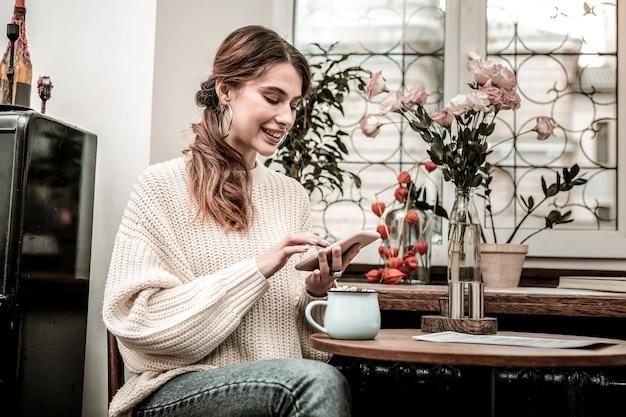 Navegar na internet. uma mulher sorridente navegando na internet usando um smartphone enquanto bebe chocolate