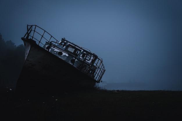 Navio abandonado em terra no meio do nevoeiro